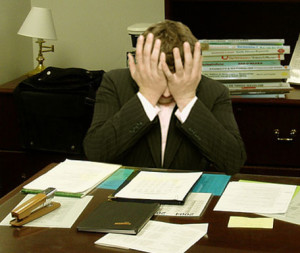 """""""Frustrated man at a desk (cropped)"""" by LaurMG. - Cropped from """"File:Frustrated man at a desk.jpg"""".. Licensed under CC BY-SA 3.0 via Wikimedia Commons."""